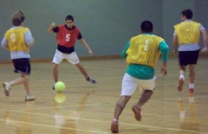 Teen Boys Passing Soccer Ball in Gym